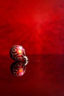Елочная игрушка для украшения елки на красном фоне.