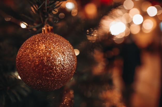 Елочная игрушка золотой шар висит на елке с размытым блестящим праздничным боке