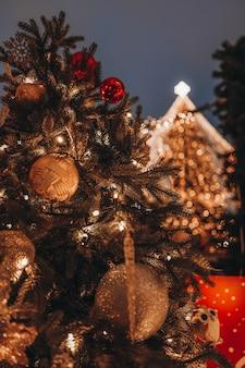 Елочная игрушка золотой шар висит на елке с блестящими огнями боке на фоне