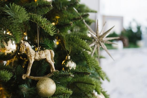 Елочная игрушка лошадь и шары висят на елке, украшенной огоньками