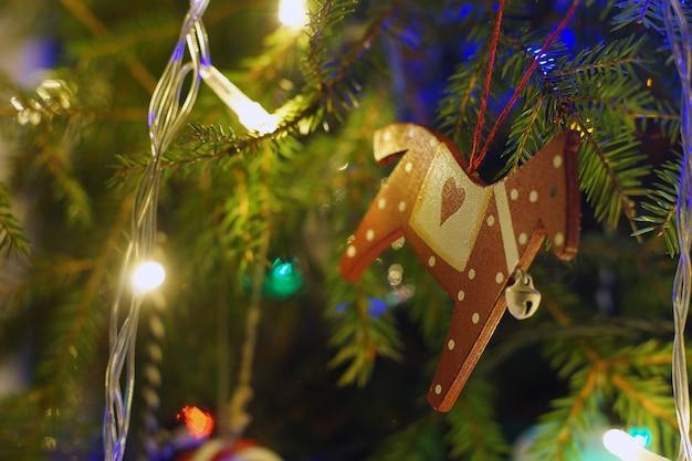 明るい花輪とクリスマスツリーの枝にぶら下がっているクリスマスのおもちゃの馬。