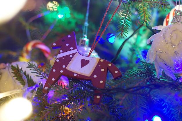 クリスマスツリーの枝にぶら下がっているクリスマスのおもちゃの馬。