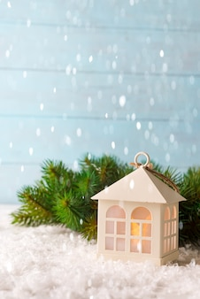 Christmas toy house , it's snowing on a natural background of a real fir in the snow.