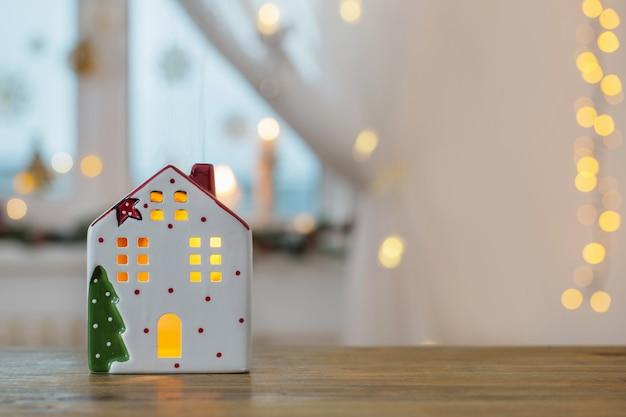 Елочные игрушки домики на фоне украшенного окна