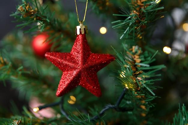Елочная игрушка в виде звезды, висящей на ветке на фоне боке из гирлянд