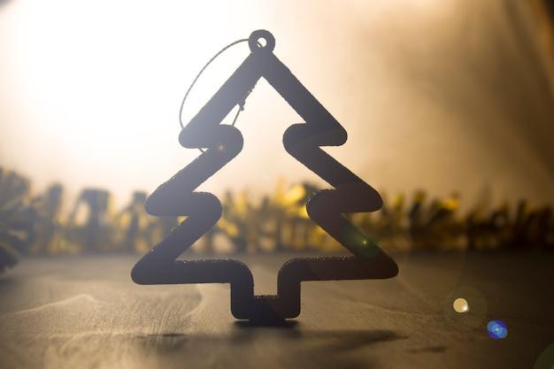 木の形のクリスマスのおもちゃ、バックライト、輝き。クリスマスデザインの背景