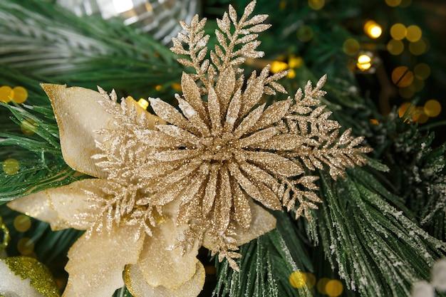 Елочная игрушка на еловой ветке в новогоднем украшении в виде цветка