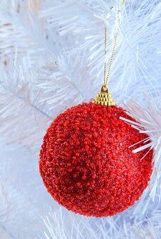 Новогодняя игрушка на крупном плане белоснежной елки, изолированной на белом