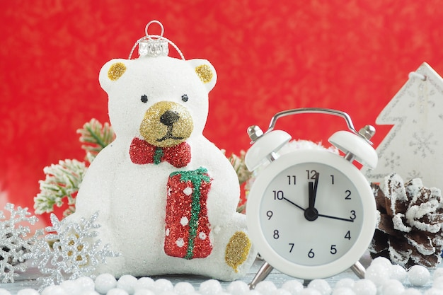 Christmas toy polar bear, alarm clock, silver snowflake, pine cone and white beads. red background.