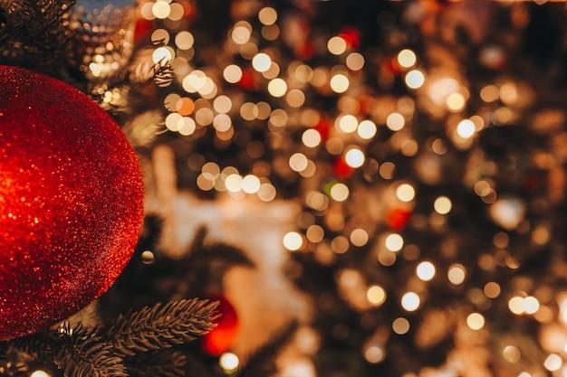 Елочная игрушка красный шар висит на елке с золотыми праздничными огнями боке на фоне