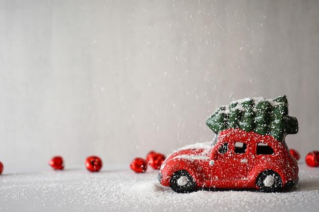Елочная игрушка красный автомобиль в снегу на сером. новогодняя композиция. copyspace.