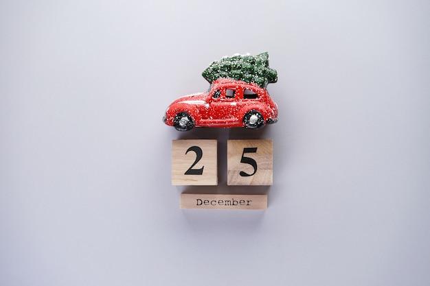 灰色の木製カレンダーとクリスマスグッズの赤い車。クリスマスの組成物。