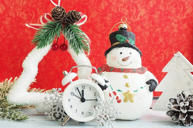 Christmas toy snowman, alarm clock, silver snowflake and tinsel on a red background.