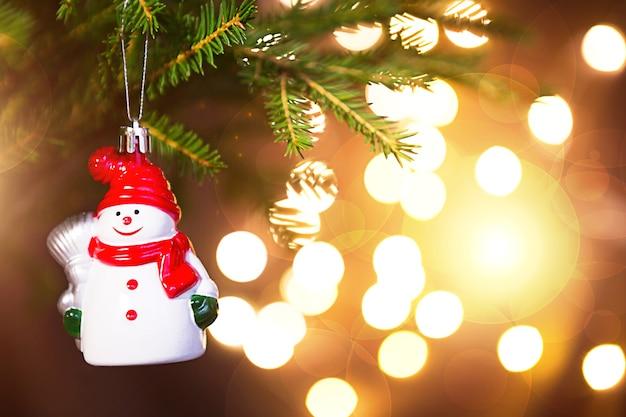 Елочная игрушка снеговик в красной шляпе с шарфом на живой ветке ели с золотыми огнями гирлянд в расфокусе. новый год, рождество, праздник фон, боке, копия пространства