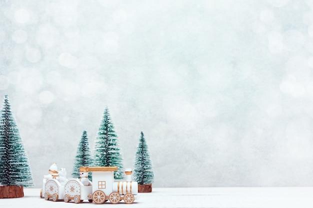 クリスマスのおもちゃの列車は、ミニチュアの雪に覆われた森を旅します