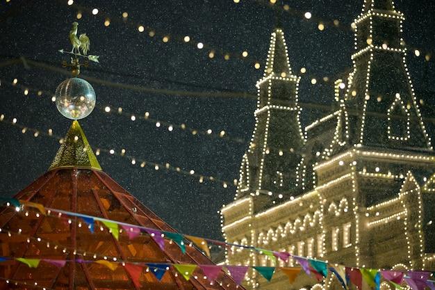Новогодние игрушки и гирлянды сверкают на фоне главного универмага гум.