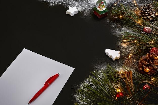 Рождественские игрушки и ноутбук, лежа возле зеленой еловой ветки на черном фоне, вид сверху. скопируйте пространство. натюрморт. плоская планировка. новый год
