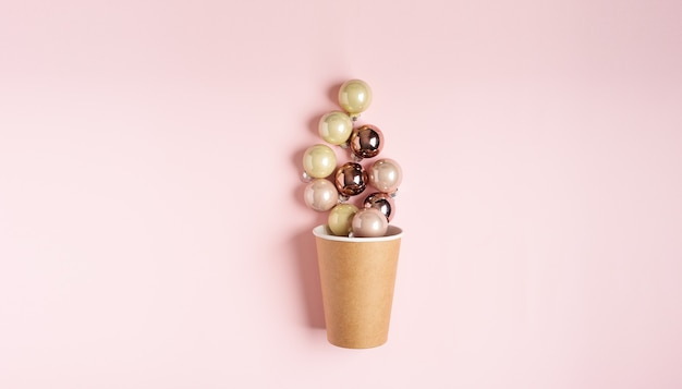 Christmas toys balls in paper cup of coffee