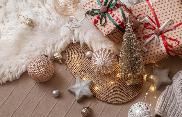 Елочные игрушки, декоративные звездочки, маленькая блестящая елочка, упакованные подарки и гирлянда на фоне домашнего интерьера.