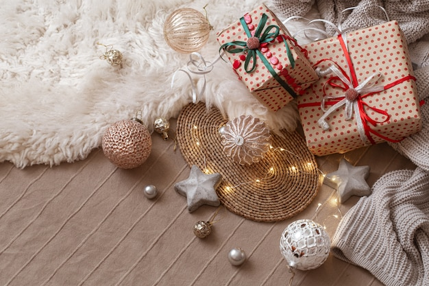 Christmas toys, decorative stars, wrapped gifts and garland on the background of the home interior.