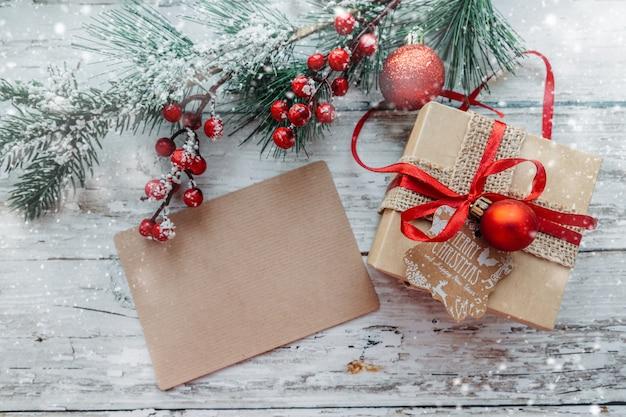Елочные игрушки-подарки с крафтовой карточкой для вставки текста на деревянном фоне со снежинками