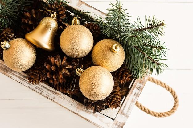 白い木製の背景にロープで作られたハンドルと白い木製の箱のクリスマスのおもちゃ、金のボールと森の円錐形。上面図。近い角度。