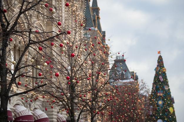 Новогодние игрушки свисают с веток, а на фасаде дома в москве сверкают гирлянды.
