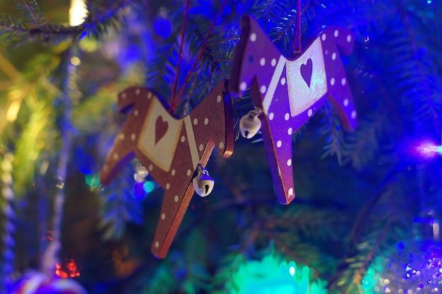 クリスマスのおもちゃは、輝く花輪に囲まれた枝にぶら下がっています。