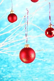 Рождественские игрушки, висящие на ветке на синем фоне