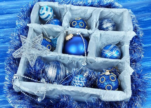 青い背景の木製の箱のクリスマスのおもちゃ
