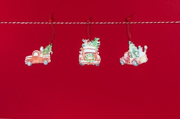빨간색 배경에 밧줄에 매달려 나무 차에 크리스마스 장난감