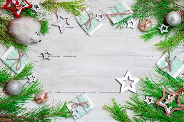 Елочные игрушки, сосновые ветки, подарочные коробки, звездочки, шары, белый игрушечный ёжик на деревянной поверхности