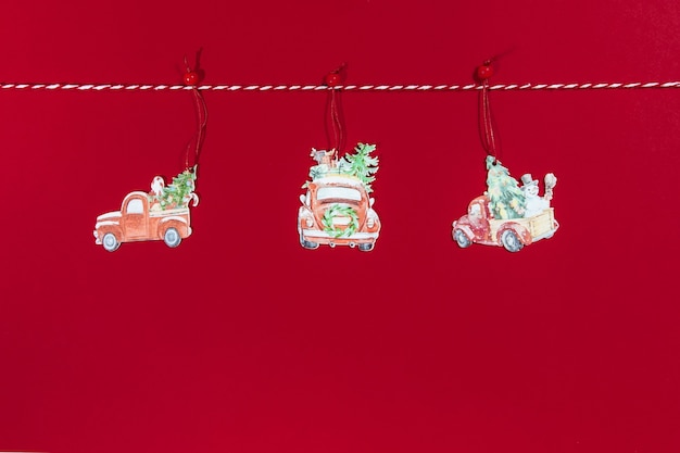 Christmas toys on the tree car hanging on the rope on a red background