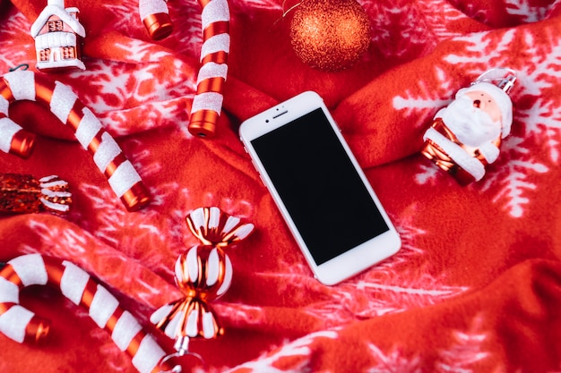 Christmas toys with smartphone on blanket