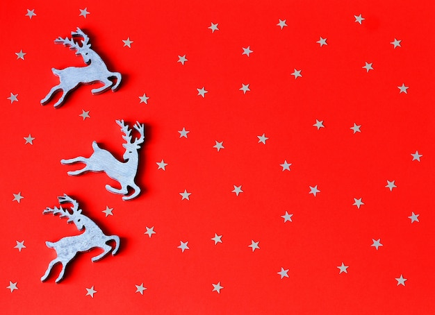 Christmas toys wooden deers on red paper background with decorative stars.