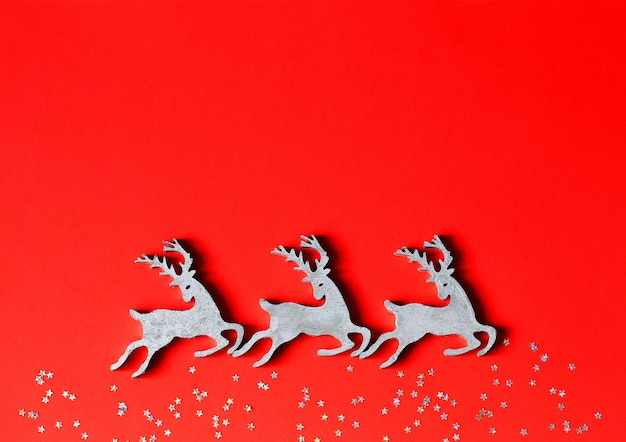 Christmas toys wooden deers on red paper background with decorative stars