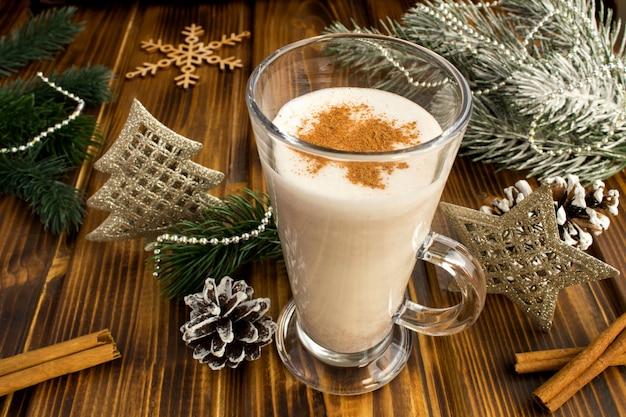 茶色の木製の背景にクリスマスの伝統エッグノッグとクリスマスの組成。閉じる。