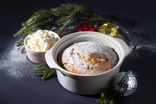 黒の背景のトウヒの枝のベーキング皿にレーズンとクリスマスの伝統的な豆腐ケーキ