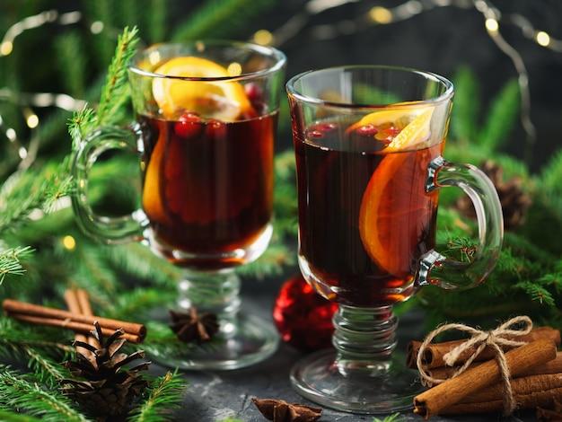 Рождественский традиционный напиток глинтвейн на столе из красного вина с апельсином, корицей, анисом и клюквой