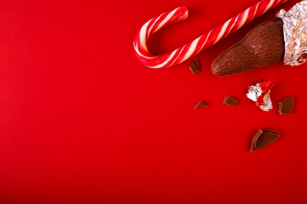 Christmas traditional sweets on red background. chocolate santa clauses with candy cane.