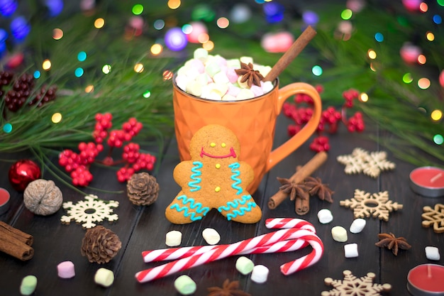 Christmas treat - gingerbread and hot chocolate with marshmallow, cinnamon, cloves on wood