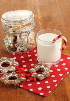 クリスマスのおやつと木製のテーブルのクローズアップのミルクのガラス