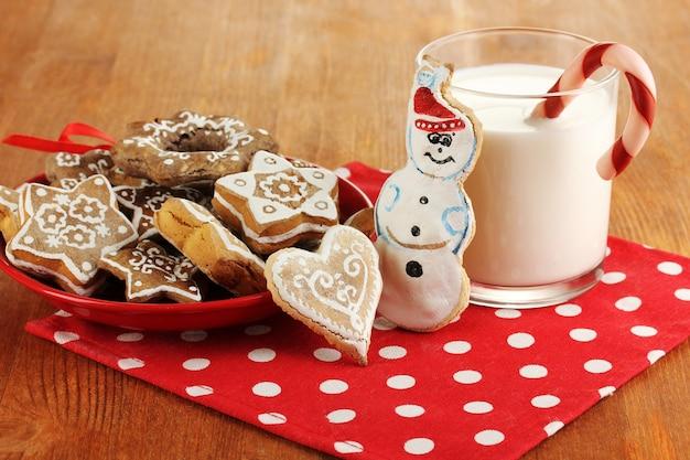 皿の上のクリスマスの御馳走と木製のテーブルのクローズアップのミルクのガラス