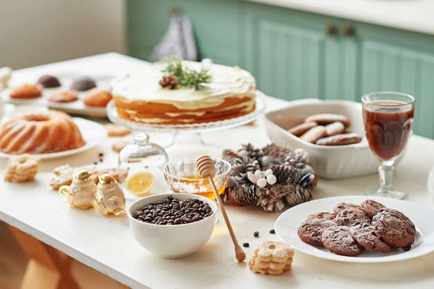 Christmas treats on the table: cupcake, naked cake, cookies and coffee with honey