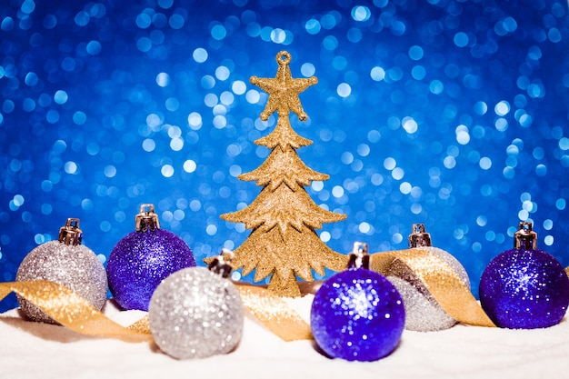 青いキラキラ背景に雪の中でクリスマスツリーとボール