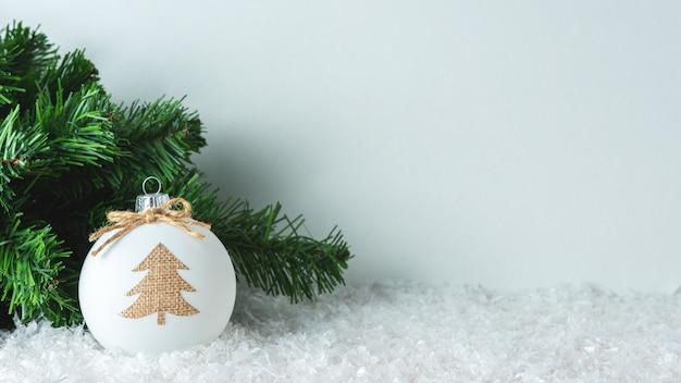 雪の上のクリスマスツリーと安物の宝石の装飾