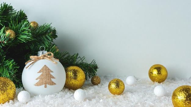 雪の上のクリスマスツリーとつまらない装飾