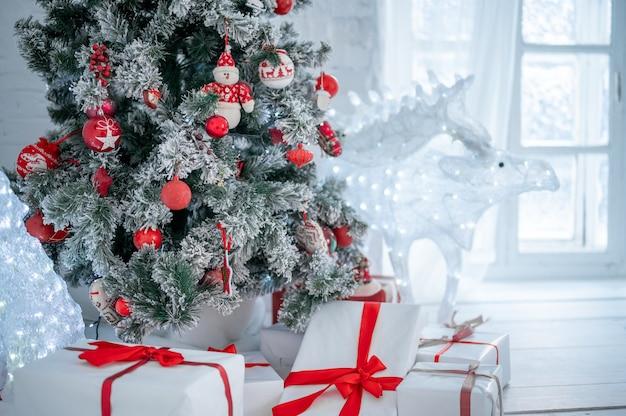鹿とインテリアのクリスマスツリーとクリスマスギフトボックス。クリスマスカード。おもちゃで飾られたクリスマスツリー、クリスマスツリーの周りに赤いリボンで結ばれた多くの贈り物。新年のクリスマスのインテリア Premium写真