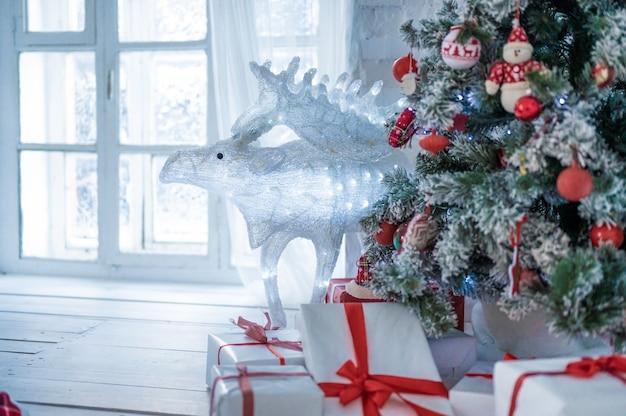 사슴과 인테리어에 크리스마스 트리와 크리스마스 선물 상자. 크리스마스 카드입니다. 장난감으로 장식된 크리스마스 트리, 크리스마스 트리 주위에 빨간 리본으로 묶인 많은 선물. 새해 크리스마스 인테리어