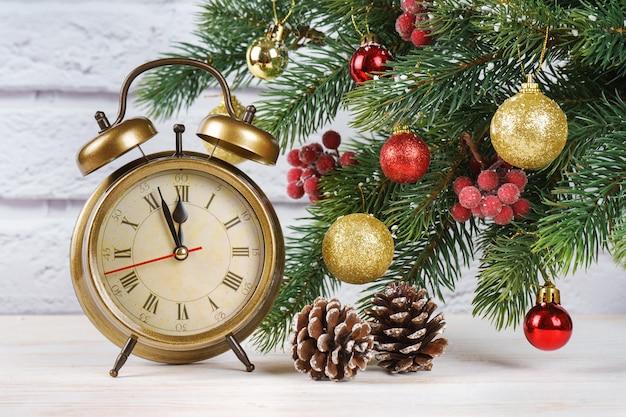 Елка и обратный отсчет до нового года. бронзовые ретро часы, конус и шары и еловые ветки ели на фоне белого кирпича.